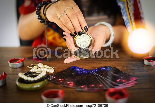 Psychic readings and clairvoyance concept - Crystal ball fortune teller with hands hold retro pocket watch and Tarot cards reading divination - csp72106736