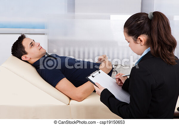 Psychologist Writing Notes While Patient Lying On Bed - csp19150653