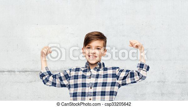 Chico feliz con camisa a cuadros mostrando puños fuertes - csp33205642