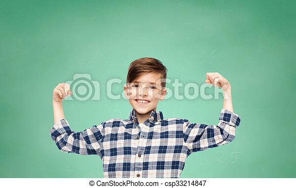 Chico feliz con camisa a cuadros mostrando puños fuertes - csp33214847