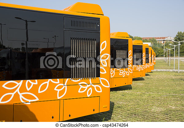 New modern busses for public transportation are shown in a row from the backs in a parking lot.