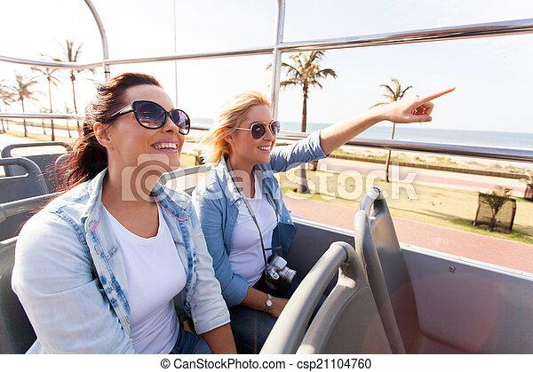 Dos amigos tomando el autobús de la ciudad de gira por el pueblo - csp21104760