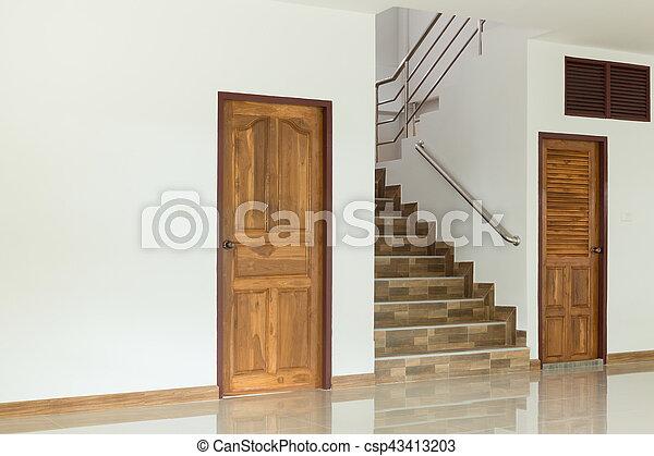 Interior blanco vacío con puerta de madera y escaleras - csp43413203