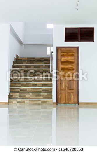 Interior blanco vacío con puerta de madera y escaleras - csp48728553