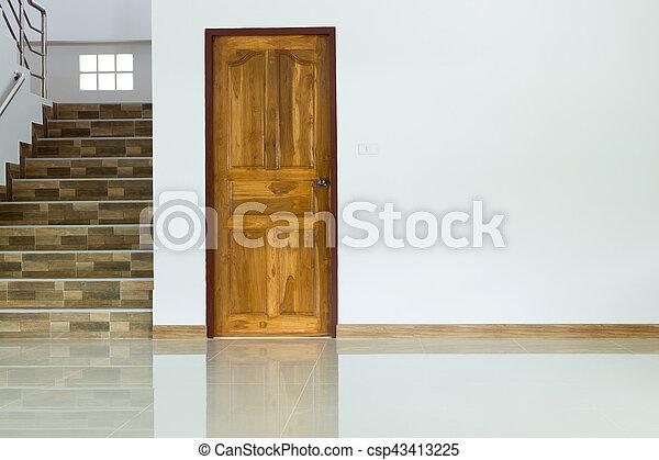 Interior blanco vacío con puerta de madera y escaleras - csp43413225