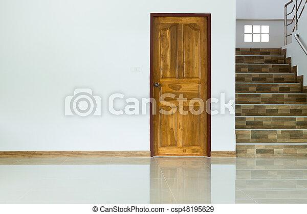 Interior blanco vacío con puerta de madera y escaleras - csp48195629