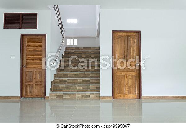 Interior blanco vacío con puerta de madera y escaleras - csp49395067