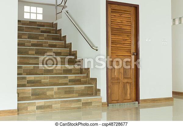 Interior blanco vacío con puerta de madera y escaleras - csp48728677