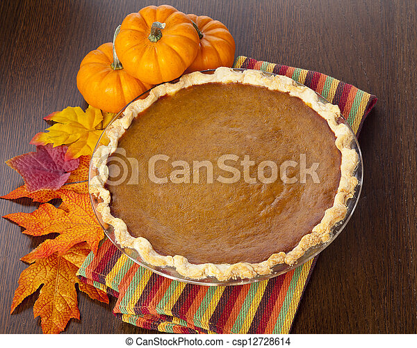 pumpkin pie on table next to pumpkins - csp12728614