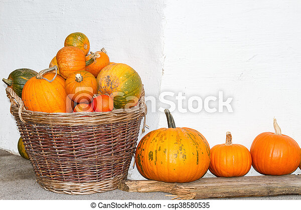 Pumpkins in a wicker basket. Autumn decoration. Outdoors image. - csp38580535