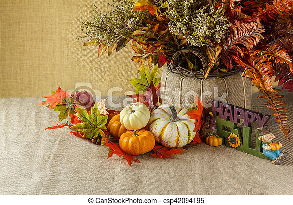 Pumpkins with fall leaves on sackcloth - csp42094195