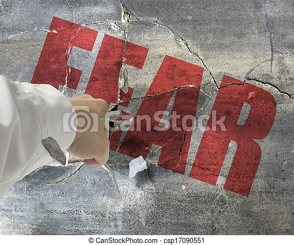 Punching, break concrete wall with word fear on it and small pieces flying out - csp17090551