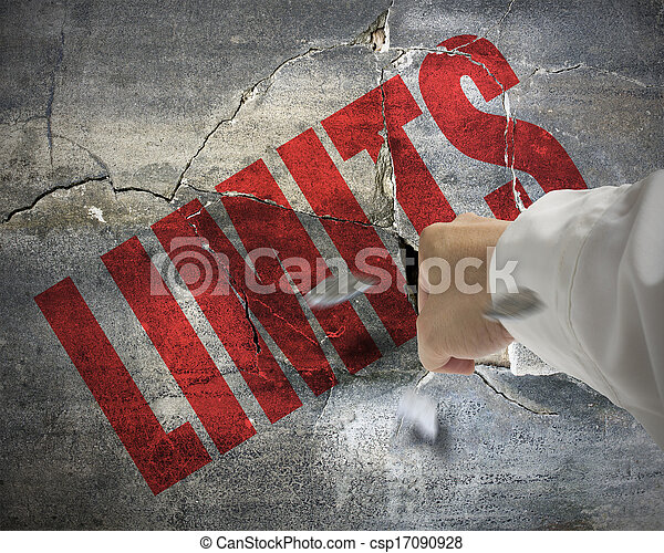 Punching, cracked concrete wall with word LIMITS on it and small pieces rock flying out - csp17090928