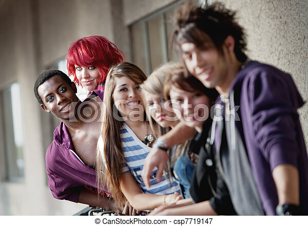 Punk rock looking teens smile at the camera as the camera focuses on the  back two individuals