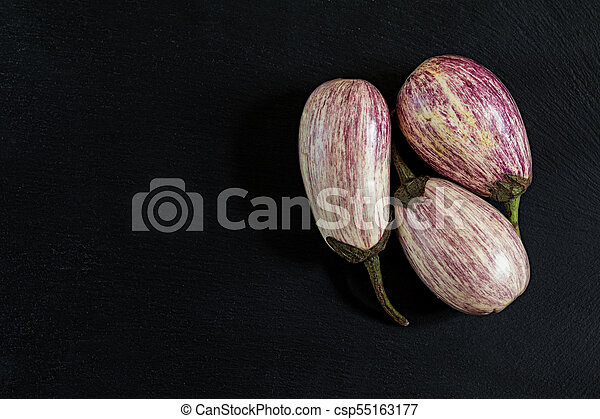 Purple graffiti three eggplants on black stone surface. Top view, copy space. - csp55163177