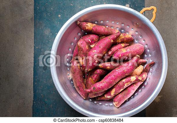 Purple sweet potato in a metal colander - csp60838484