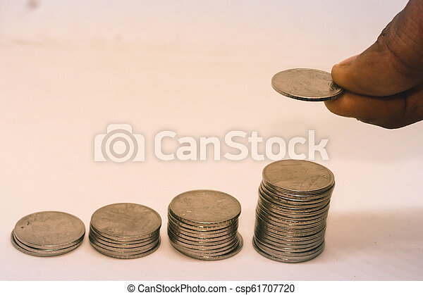 Putting a coin over a stack of coins. Isolated on white background. Concept of money management - csp61707720