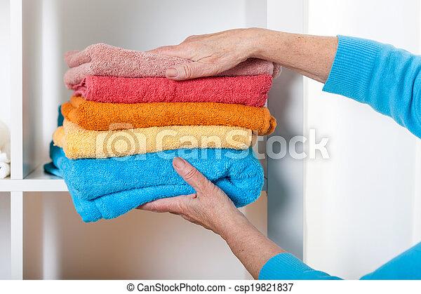 Putting towels on shelf - csp19821837
