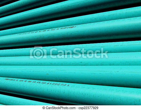 PVC plastic pipe stacked at the construction site ready to be laid as a sewer line; bright highlights and deep shadows make interesting abstract pattern. Good background for your text. - csp22377929