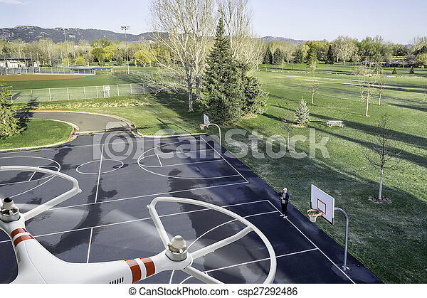 quadcopter drone flying over basketball court - csp27292486