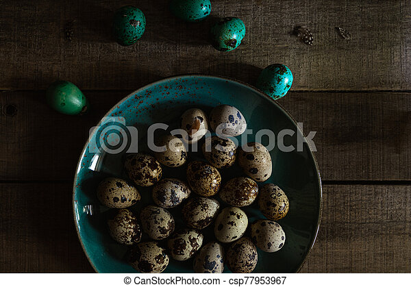Quail eggs in teal colored plate, colored eggs on wooden rustic background, closeup view - csp77953967