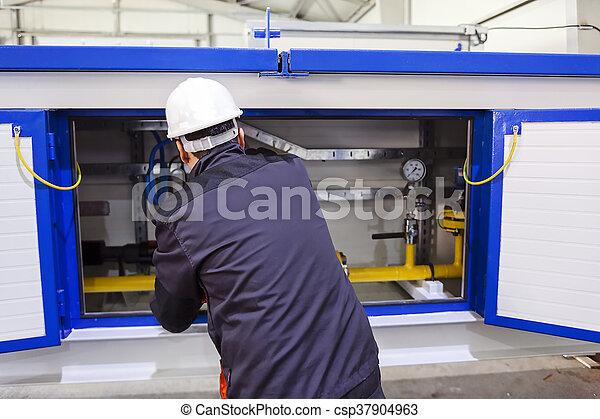 Man worker in a safety clothes performing quality control in production hall; note shallow depth of field