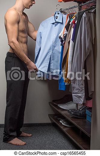 El modelo masculino adecuado es elegir una camisa. Sigue con el torso desnudo - csp16565455