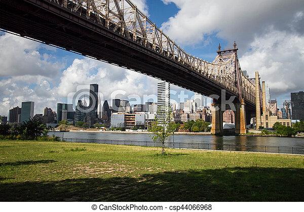 Queensboro Bridge and Manhattan city with cloudy blue sky, New York - csp44066968
