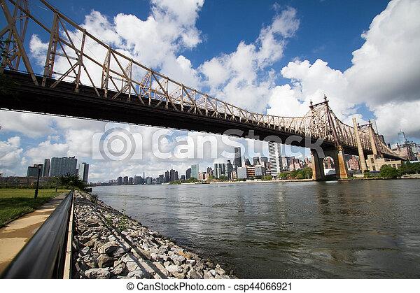 Queensboro bridge over river and shore with cloudy sky - csp44066921
