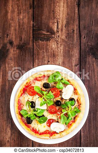 Una deliciosa pizza italiana con queso servido en la mesa de madera - csp34072813