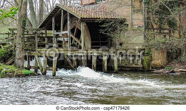 Un viejo molino de agua rústica con un pequeño arroyo - csp47179426