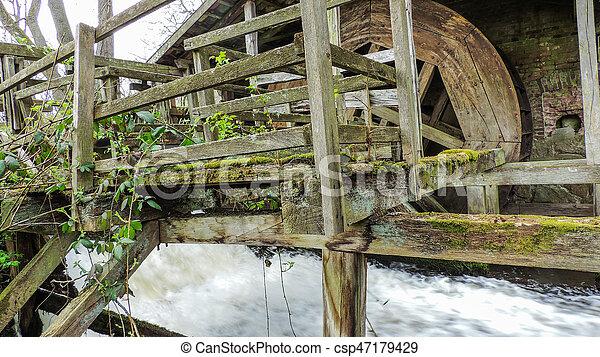 Un viejo molino de agua rústica con un pequeño arroyo - csp47179429