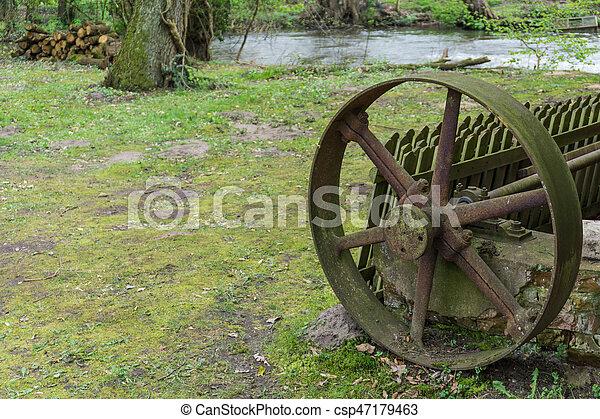 Un viejo molino de agua rústica con un pequeño arroyo - csp47179463