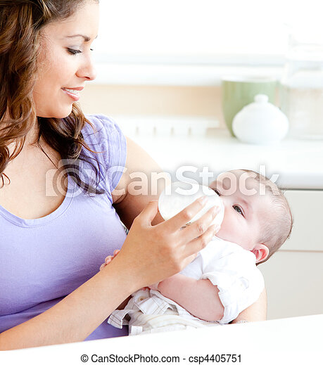 Radiant mother feeding her adorable son in the kitchen - csp4405751