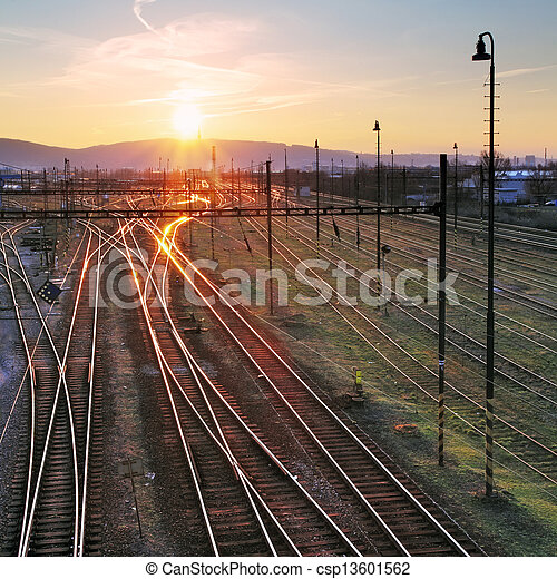 Railroad with train at sunset and many lines - csp13601562