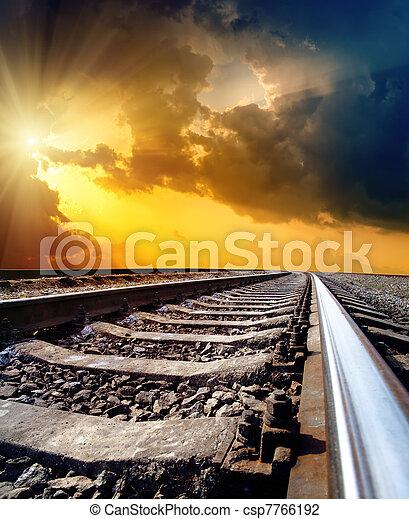 railway to horizon under dramatic sky with sun - csp7766192