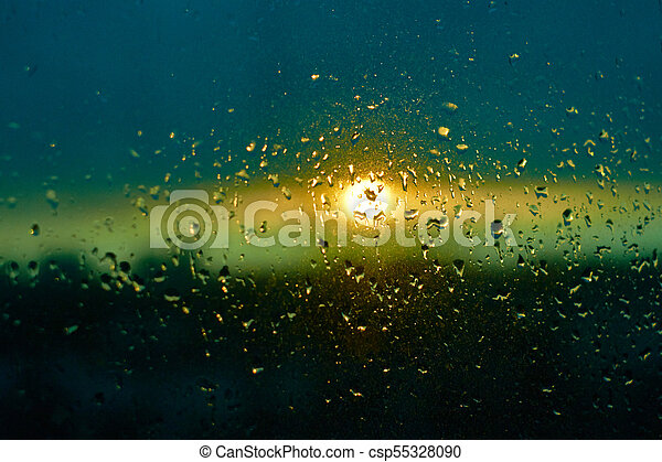 Rain Drops Texture On Window Glass With Stunning Colorful Blue Green Sunset Light Abstract Blurred Cityscape Skyline Bokeh Background Soft Focus