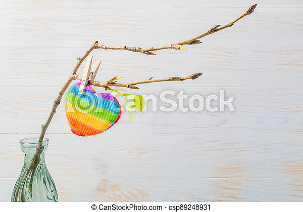 Rainbow heart shape pillow on clothespin hanging on branch with fresh leaves. Valentines day concept for LGBT. - csp89248931