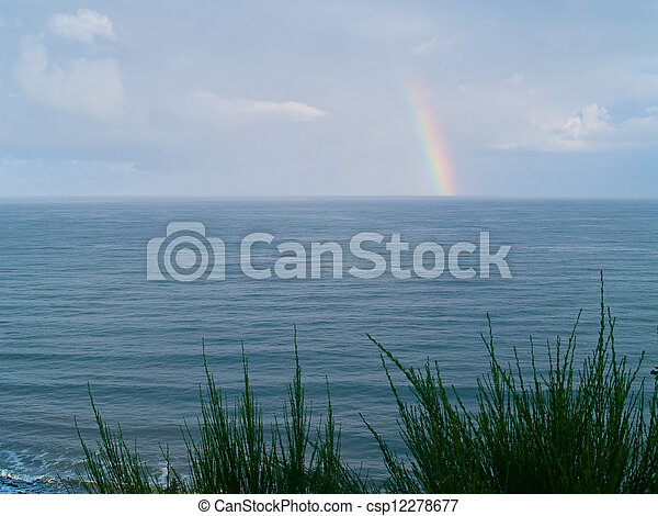 Rainbow Over the Ocean with a Partly Cloudy Sky - csp12278677