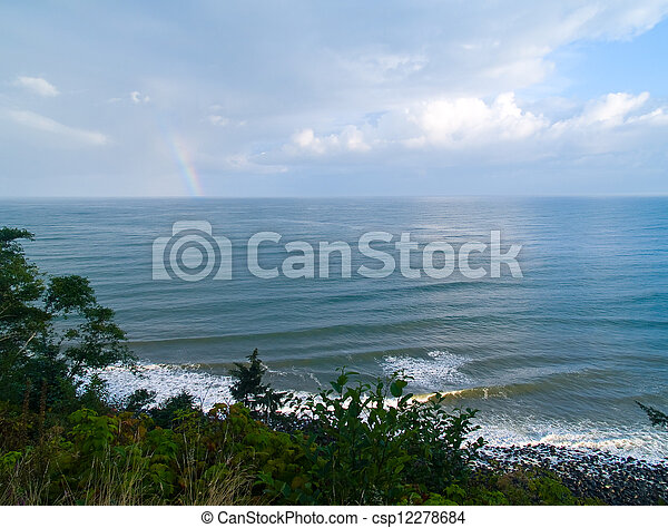 Rainbow Over the Ocean with a Partly Cloudy Sky - csp12278684