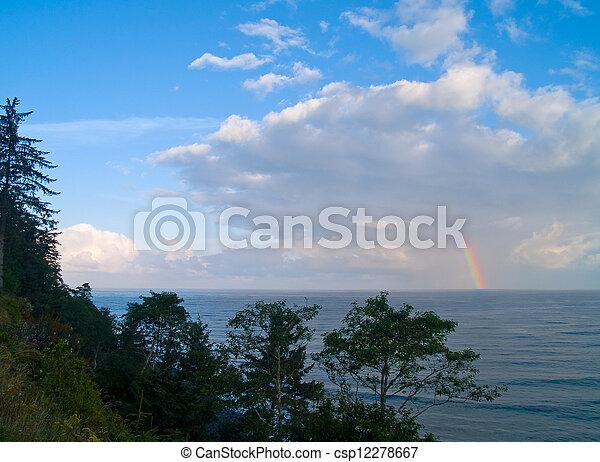Rainbow Over the Ocean with a Partly Cloudy Sky - csp12278667
