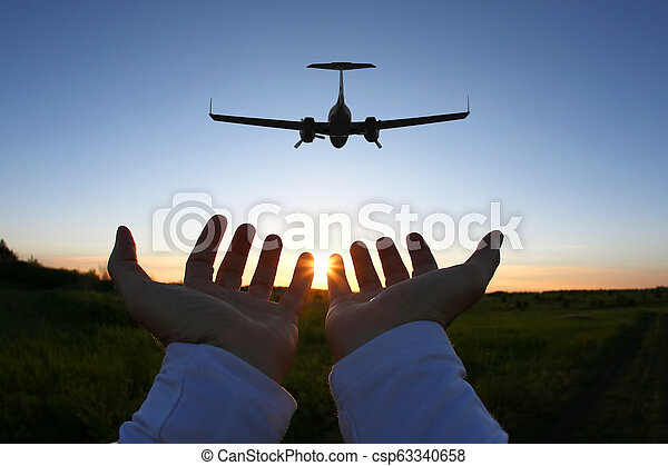 raised hands on the background of a passenger plane flying at sunset - csp63340658
