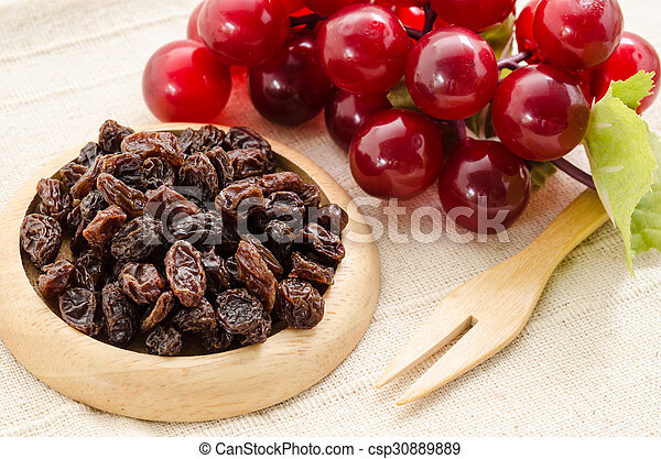 Raisins on a wooden dish and fresh red grapes. - csp30889889