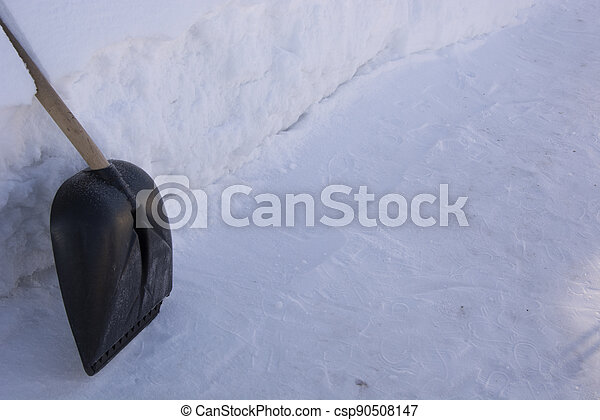 Raking away the snow in the garden. The shovel stands at a high snowdrift. There is a lot of snow in the garden in winter. - csp90508147