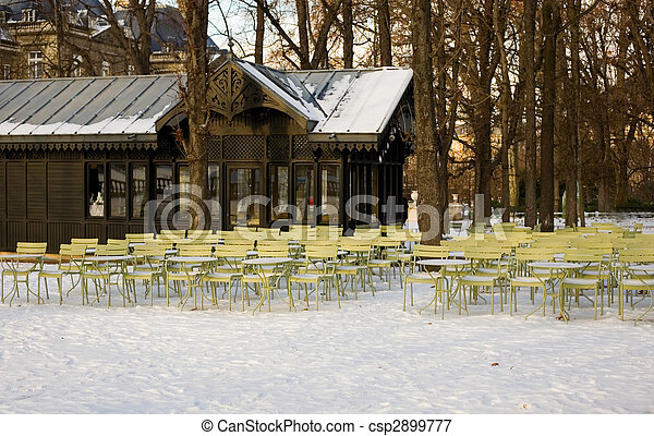 Rare snowy day in Paris. Empty street cafe and lots of snow in the Luxembourg Garden - csp2899777