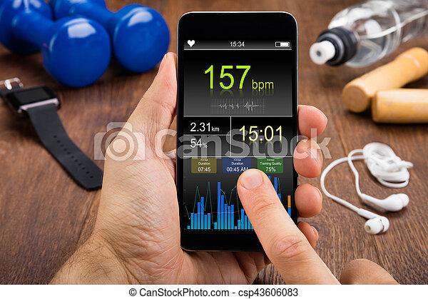 Persona comprobando la frecuencia cardíaca en el móvil - csp43606083