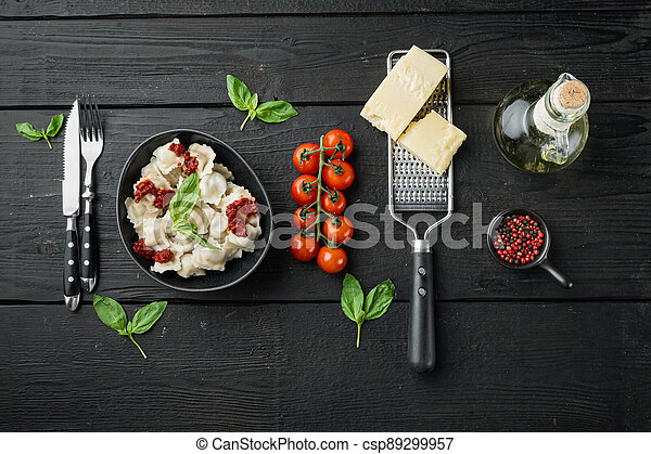 Ravioli pasta with mushroom cream sauce and cheese - Italian food style with basil parmesan and tomatoe in black bowl, on black wooden table background , top view flat lay , with copyspace and space for text - csp89299957