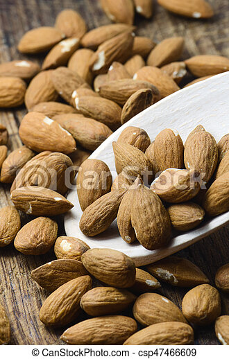 Raw almond on wooden spoon in brown background - csp47466609