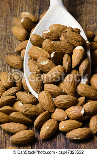 Raw almond on wooden spoon in brown background - csp47323532