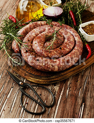 raw beef sausages on a cast-iron pan,  selective focus - csp35567671